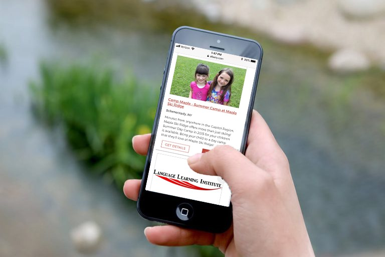 a hand holding an iphone with Albany.com's summer camp listings displayed on the screen