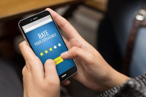 Customer using a smartphone to leave a positive hotel review to rate her experience.