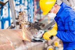 Metal worker in factory grinding metal of pipeline