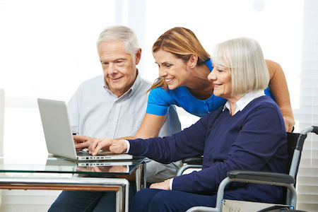 daughter helping senior couple view senior living community website on computer