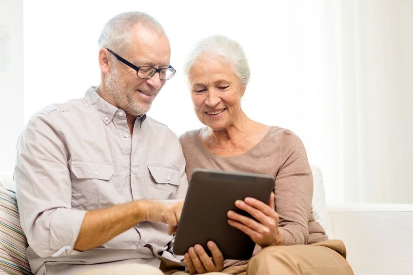 happy senior couple with tablet at home