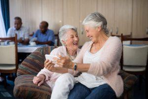 Happy senior woman taking selfie through mobile phone while sitting on sofa at nursing home
