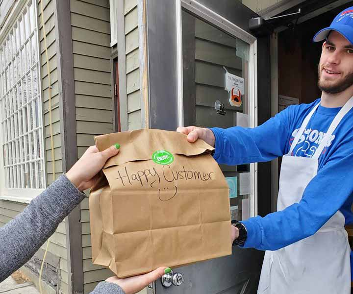 Ravenous employee handing takeout bag to customer