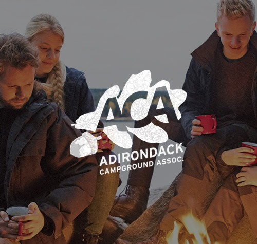 group of people sitting around campfire with ACA logo