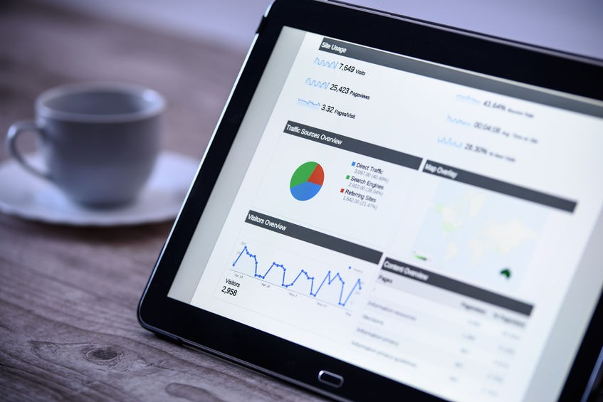 Charts and analytical data on the tablet screen with a cup of coffee on a wooden vintage table